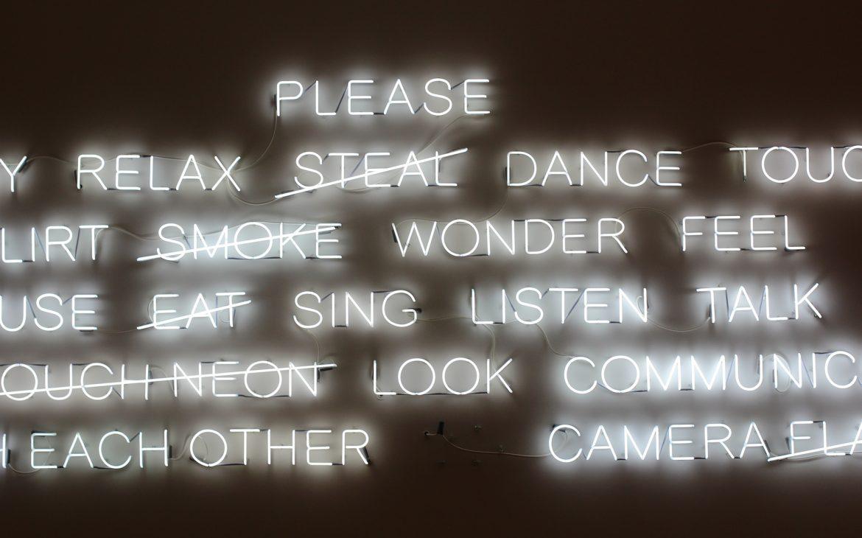 Witte neon-verlichtingen met verschillende teksten aan de wand. Woorden zoals: please, relax, dance, listen talk.