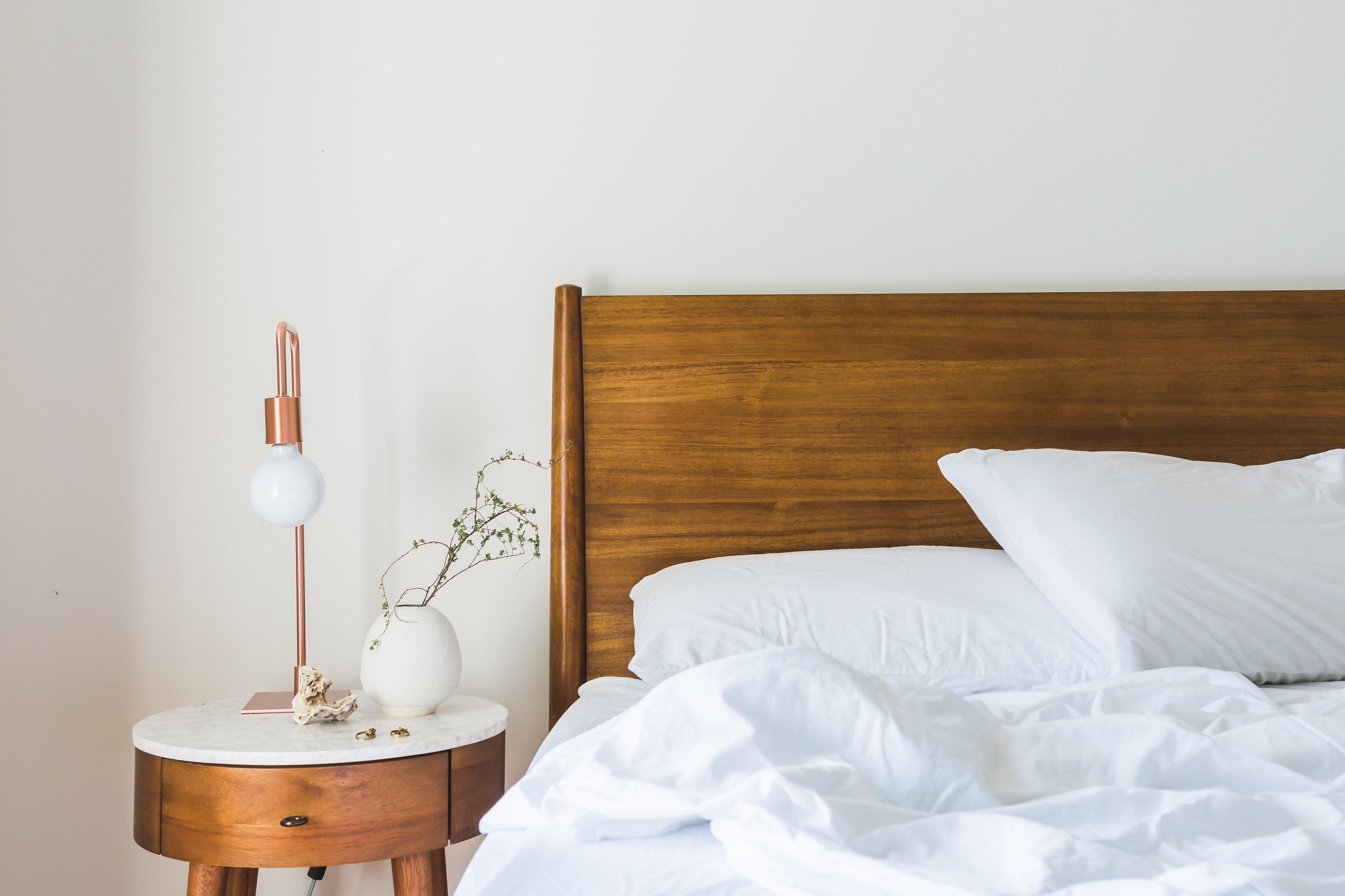 Een houten bed en nachtkastje met wit textiel. Slaapkamer inspiratie