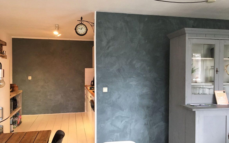 Keuken en huiskamer met betonlook muren. Grijs, blauwe betonlook muren met betonlook effect in een appartement