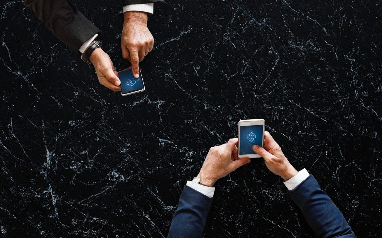 zwart marmeren ondergrond met twee telefoons van mannen
