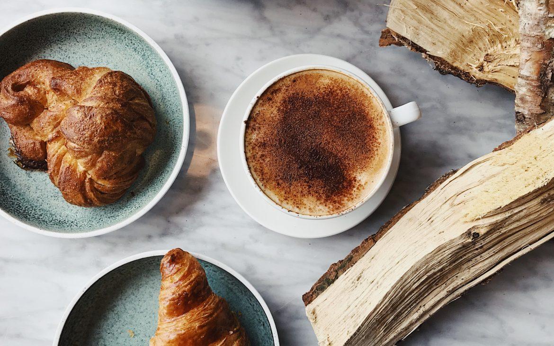 Koffie, broodje en croissant met marmeren keukenblad