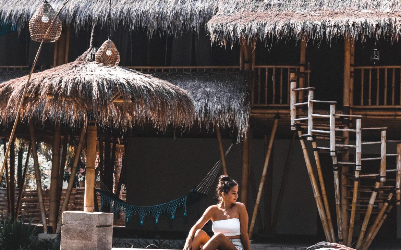Bali vibes, meisje in bikini, witte bikini en rieten daken en parasols bij een hotels.