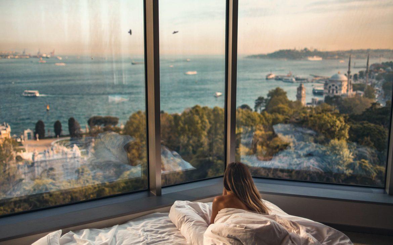 Uitzicht van meisje in bed kijken naar de haven of meer vanuit transparante, grote ramen. In hotels