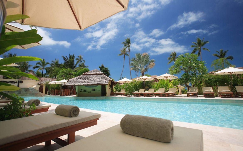 Zwembad, vakantie, handdoeken en ligbedden. Palmbomen aan hotels.