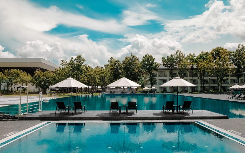 Zwembad met parasols en ligbedden. Bomen en blauwe lucht aan hotels.