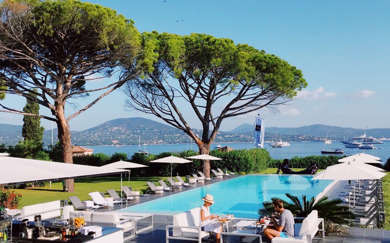 Luxe strak zwembad bij de haven, met ligbedden en loungesets aan hotels