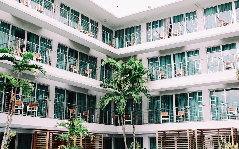 Hotels aanzicht met balkons, palmbomen en stoelen